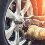 mechanic drilling car wheel
